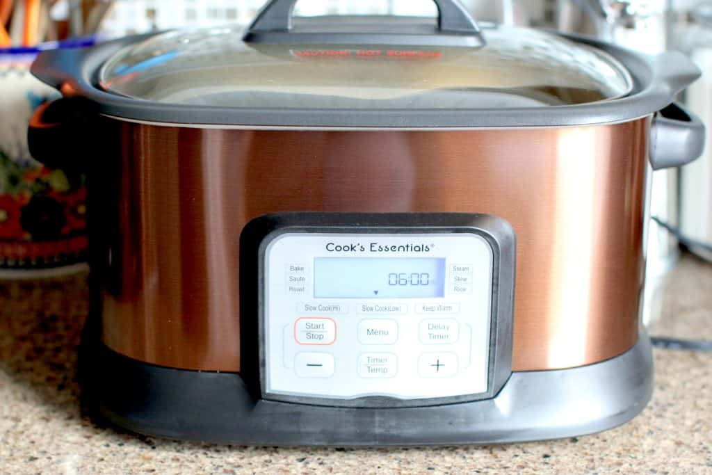 digital copper colored slow cooker showing a 6 hour timer on the digital display
