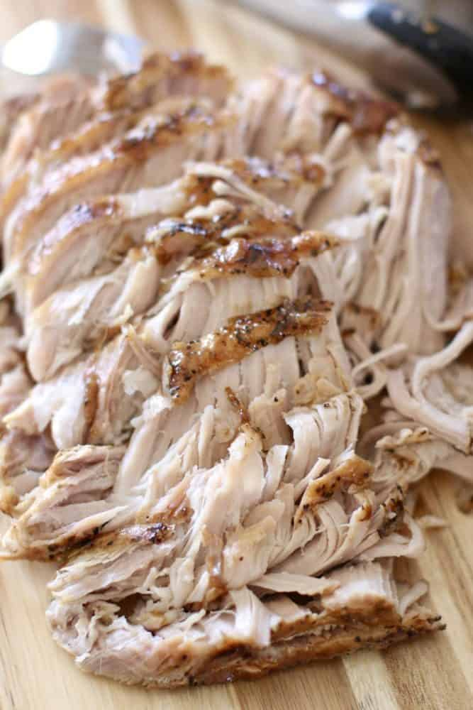 shredded cooked pork roast on a woodcutting board.
