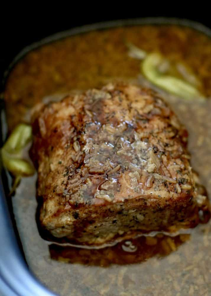 fully cooked pork roast in a slow cooker with juices