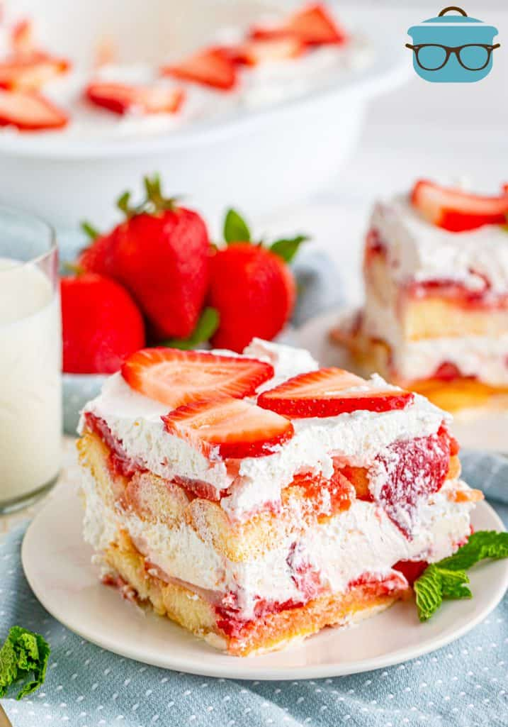 slice of strawberry tiramisu dessert shown on a small white round plate with a sprig of min t and a bowl of fresh strawberries are shown on the side