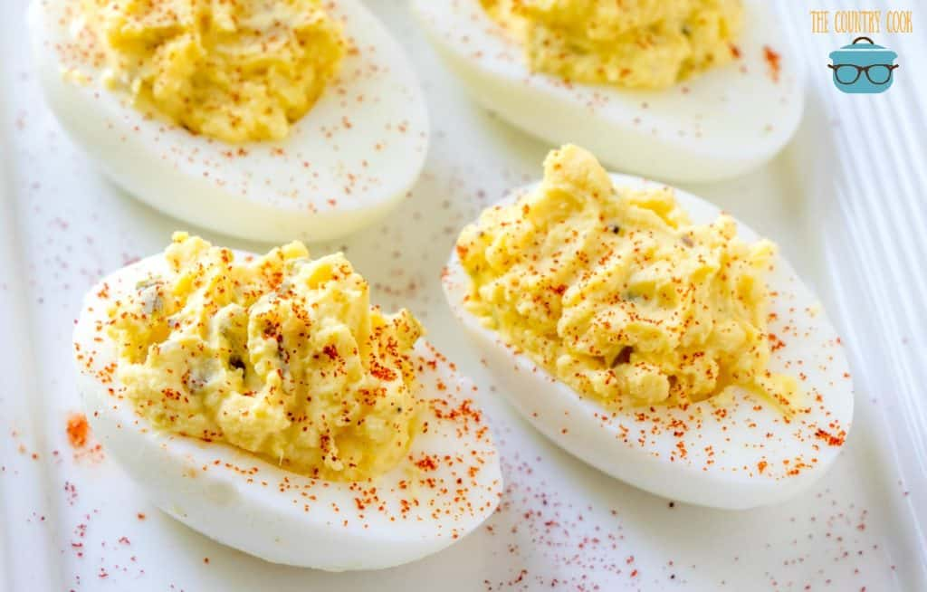 classic deviled eggs sprinkled with paprika on a white plate