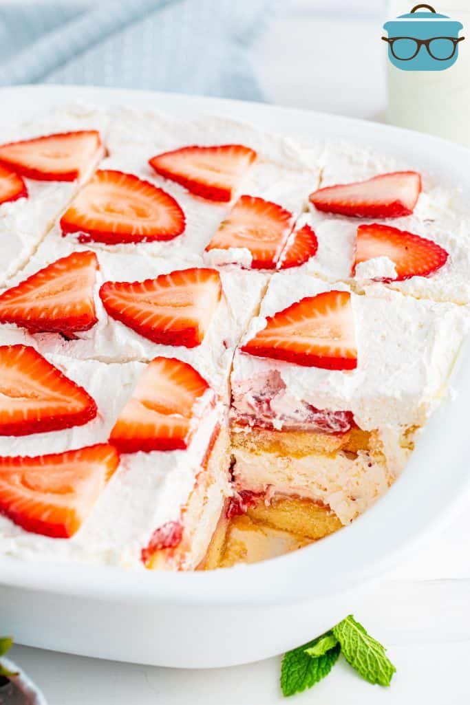 sliced strawberry tiramisu in a white dish and cut into slices with one slice removed to show interior of dessert