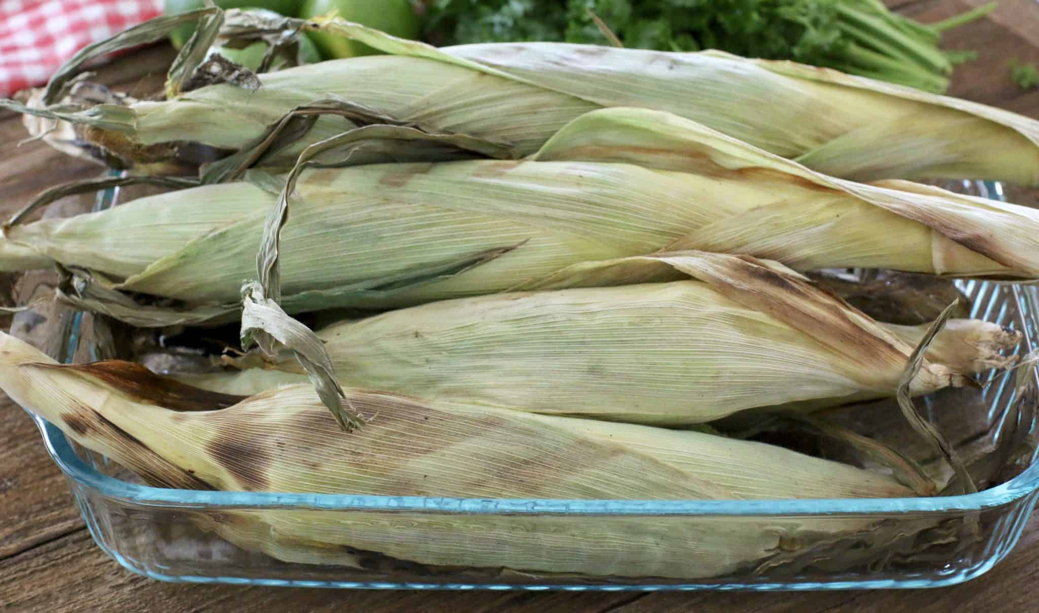 full cooked corn shown in the husks and int a baking dish.