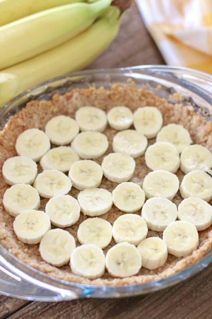 sliced bananas layered on top of vanilla wafer crust mixture