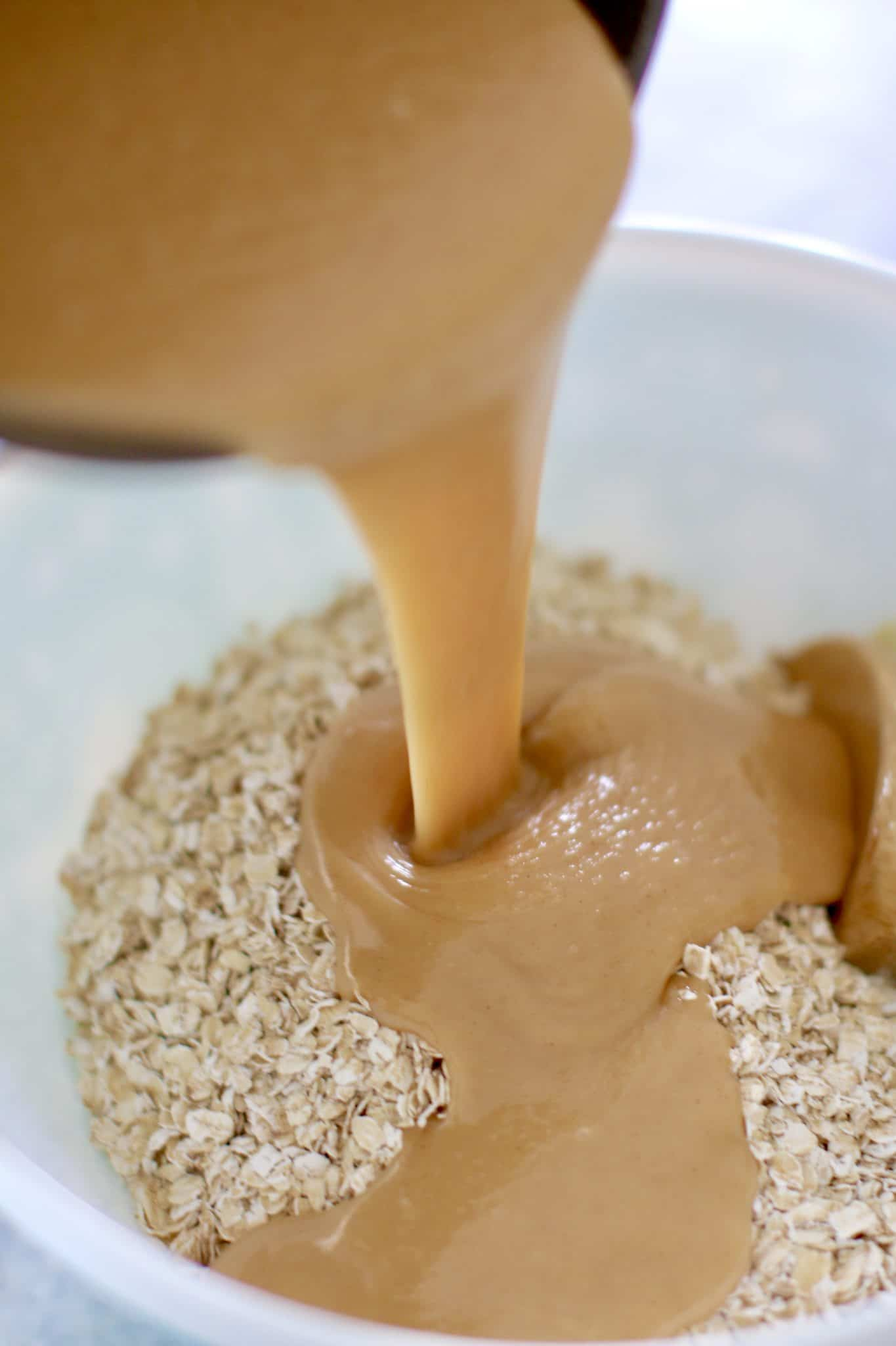 warm peanut butter mixture being poured over quick cooking oatmeal in a bowl