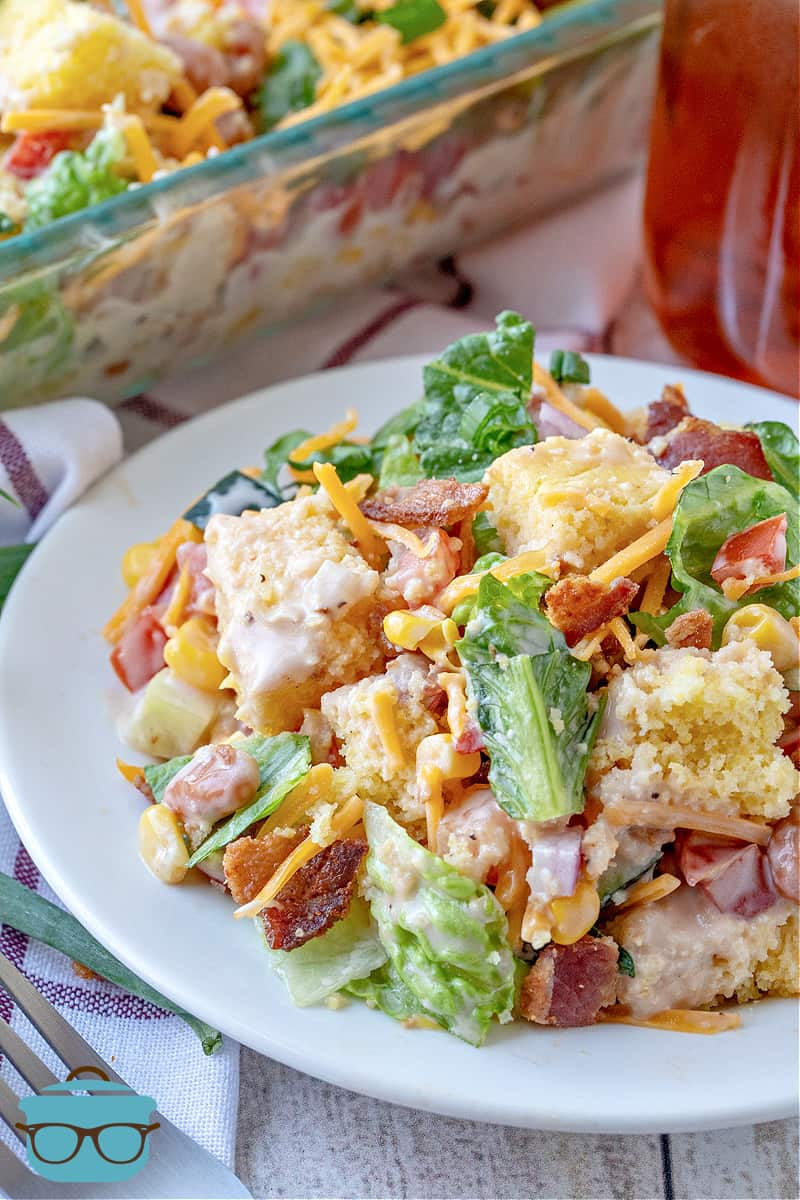 Cornbread salad serving shown on a white plate with a mason jar of iced tea in the background.