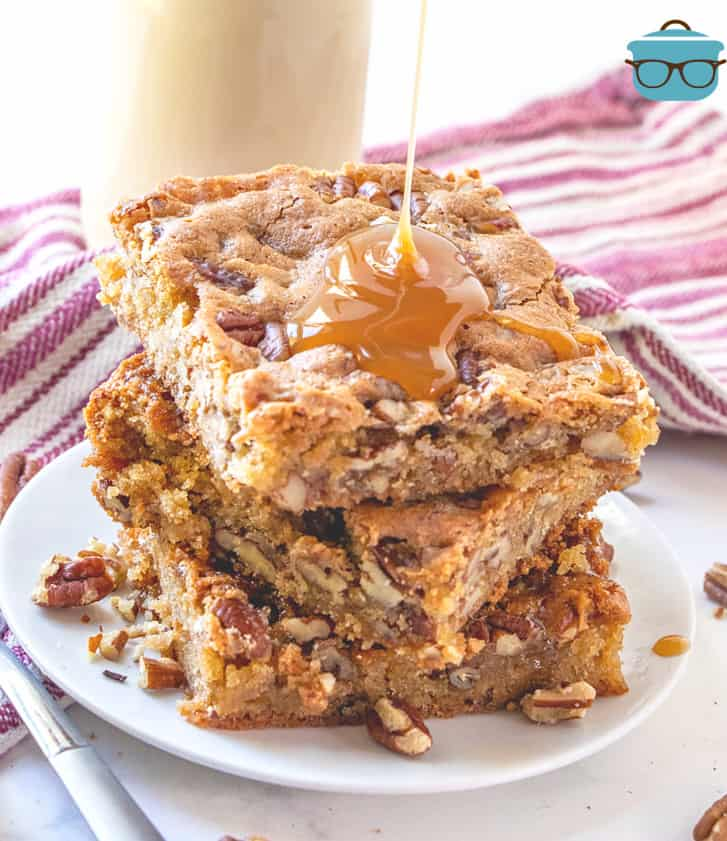 pecan cake bars stacked three on a small white plate with caramel sauce drizzling on top