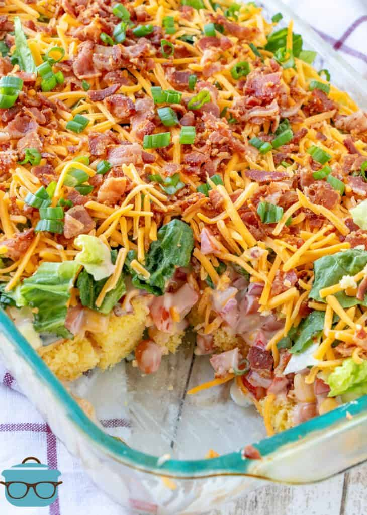 cake pan southern cornbread salad shown in a glass baking dish with a portion of salad removed to show layers of salad