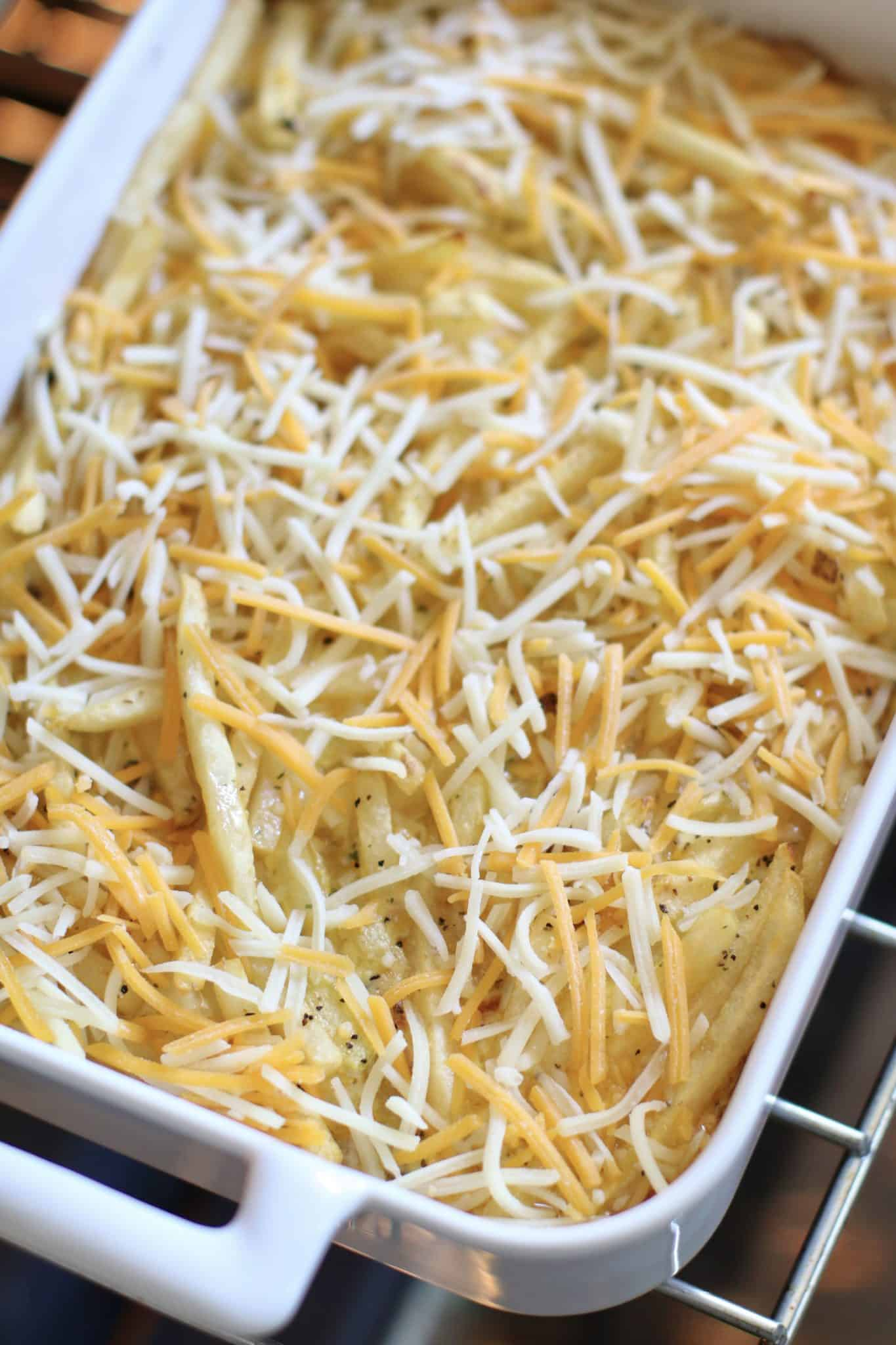 shredded cheese sprinkled onto cooked cheeseburger casserole.