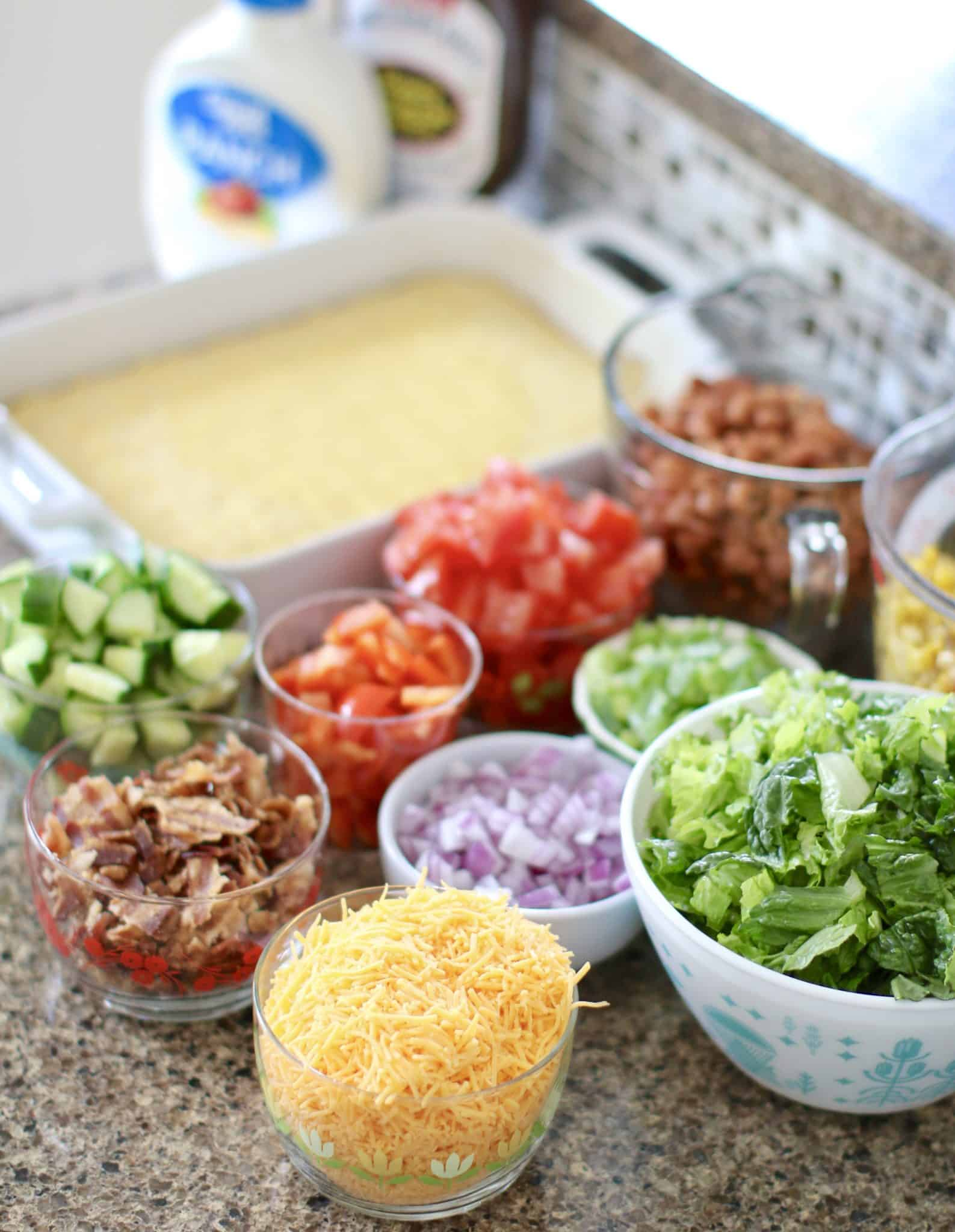 cornbread salad ingredients: cornbread mix, pinto beans, corn, Roma tomatoes, red bell pepper, cucumber, red onion, ranch dressing, barbecue sauce, romaine lettuce heart, shredded cheddar cheese, bacon, sliced green onion.