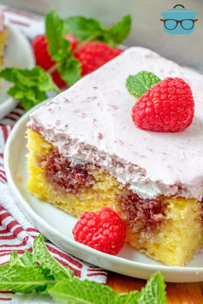 Lemon Raspberry Poke Cake - slice shown on a white plate, slice topped with a fresh raspberry with a mint leaf