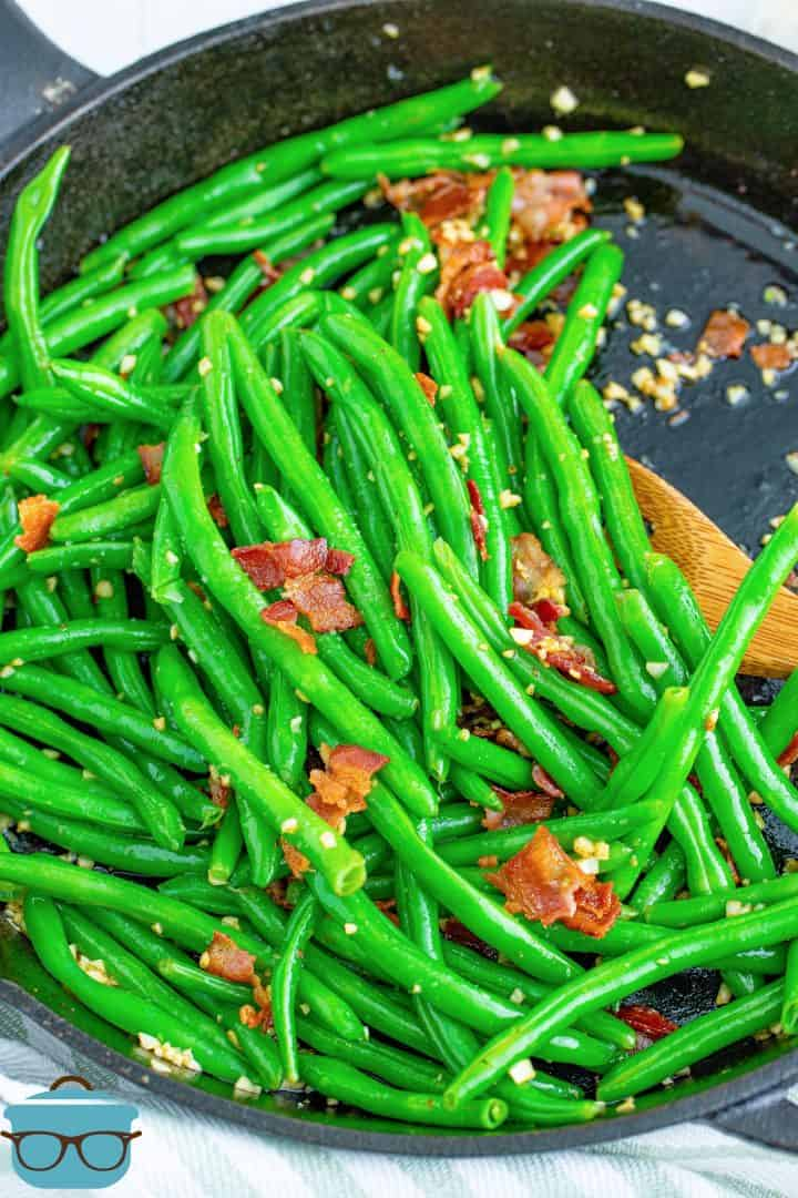 Bacon Garlic Green Beans shown fully cooked in a cast iron skillet