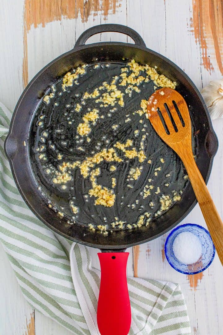 bacon grease, melted butter and minced garlic shown in a cast iron skillet with a wooden spatula