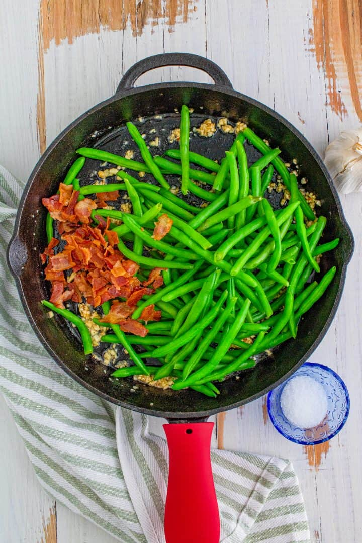 crumbled bacon and cooked green beans added into the cast iron skillet with minced garlic