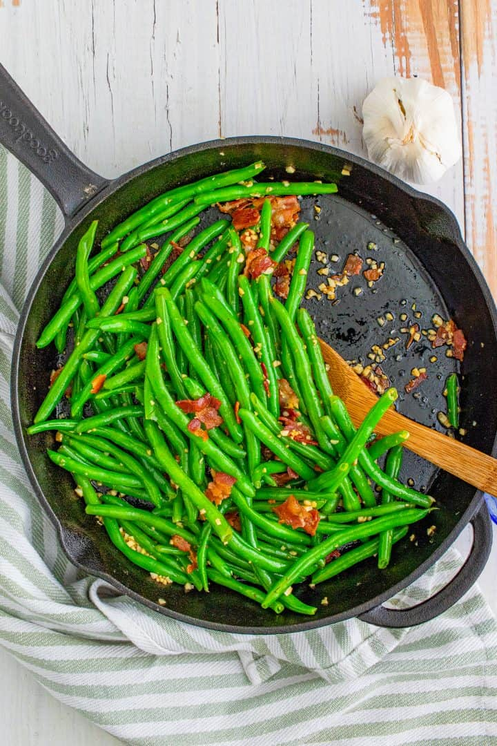fully cooked green beans and bacon in a cast iron skillet