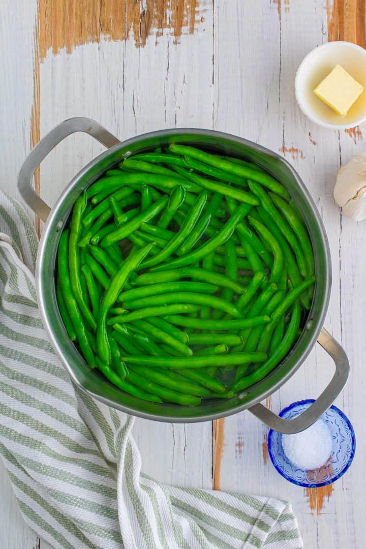 fresh green beans shown in a pot of water