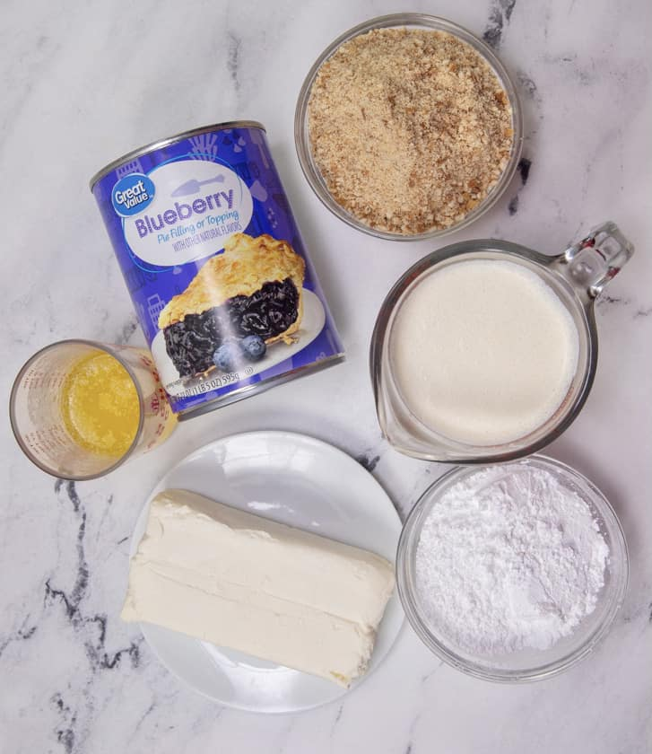 ingredients for blueberry cream cheese bars: vanilla wafers, melted butter, cream cheese, heavy whipping cream, powdered sugar, blueberry pie filling