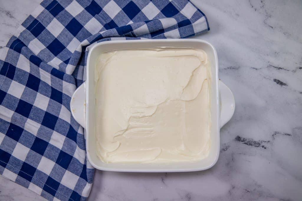 sweetened cream cheese spread over vanilla wafer crust in white square baking dish