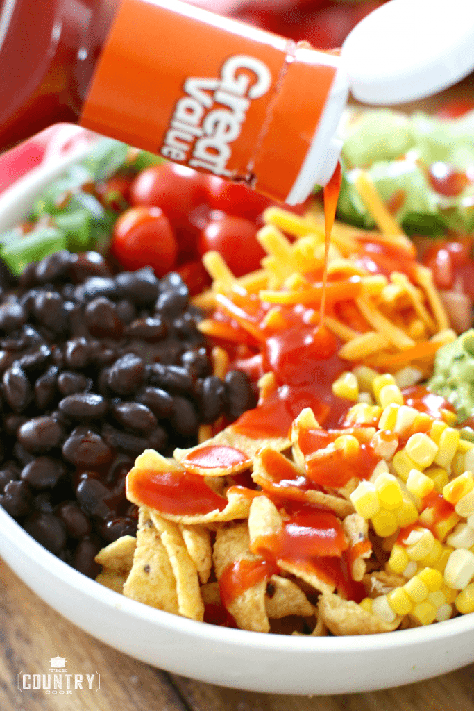 Pouring French dressing over Vegetarian Taco Salad