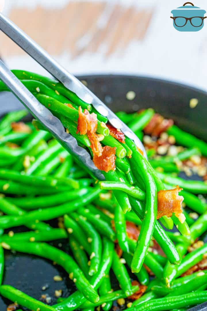 a pair of metal tongs grabbing a portion of bacon green beans out of a cast iron skillet