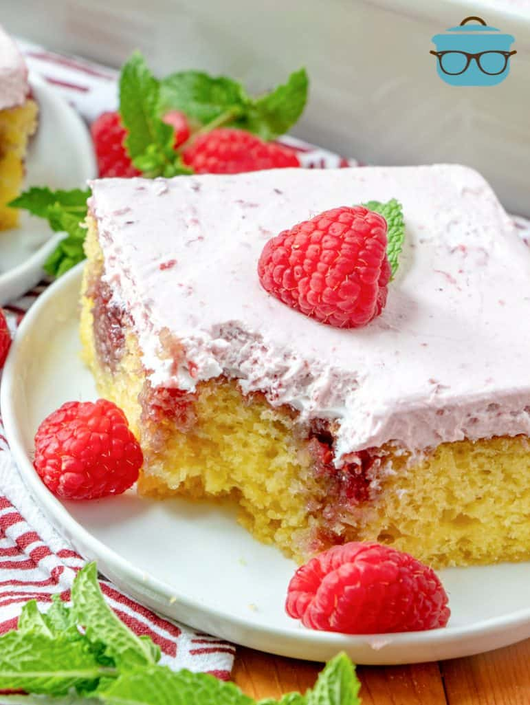 slice of Lemon Raspberry Poke Cake on a white plate with a bite cut out