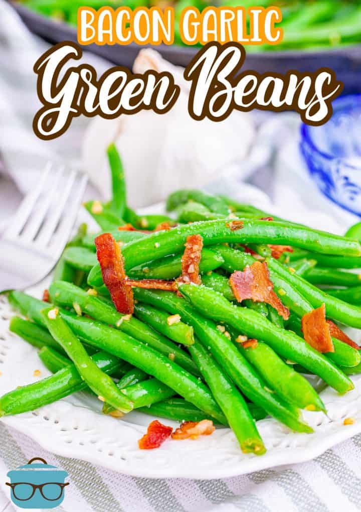 Bacon Green Beans recipe from The Country Cook, a serving of bacon green beans show in a white round plate with a bulb of garlic in the background