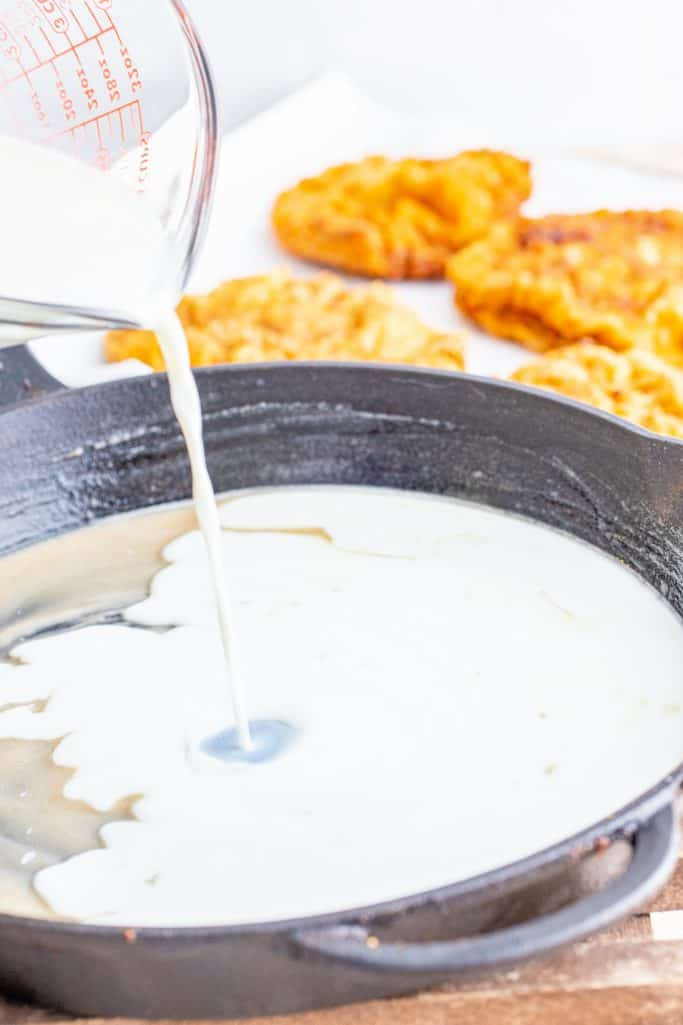pouring milk into flour mixture in cast iron pan