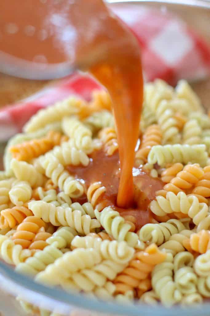 pouring dressing over pasta salad