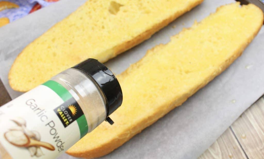 sprinkling garlic powder on bread