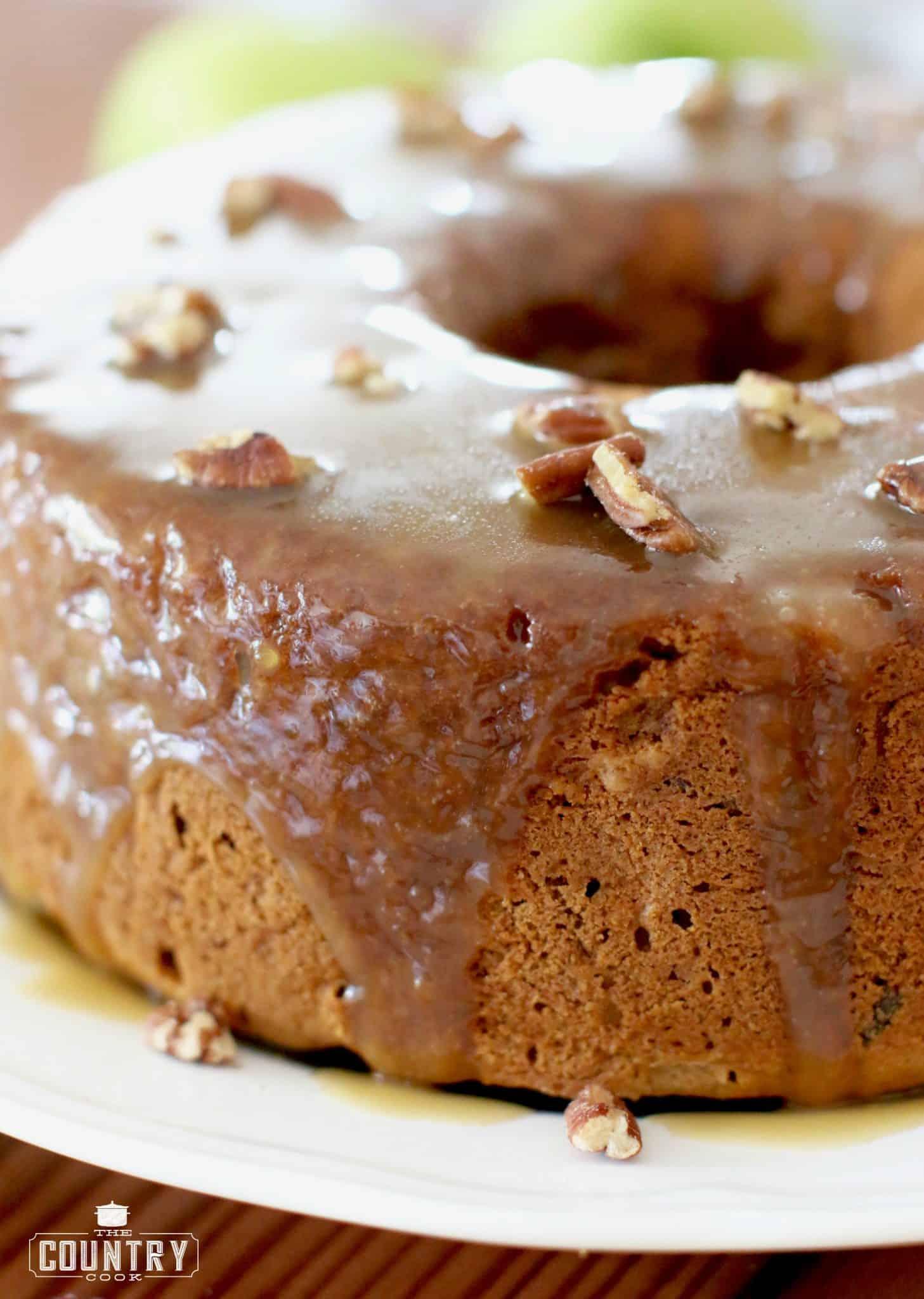Homemade Caramel Apple Cake shown fully baked and glazed on a large white serving platter.