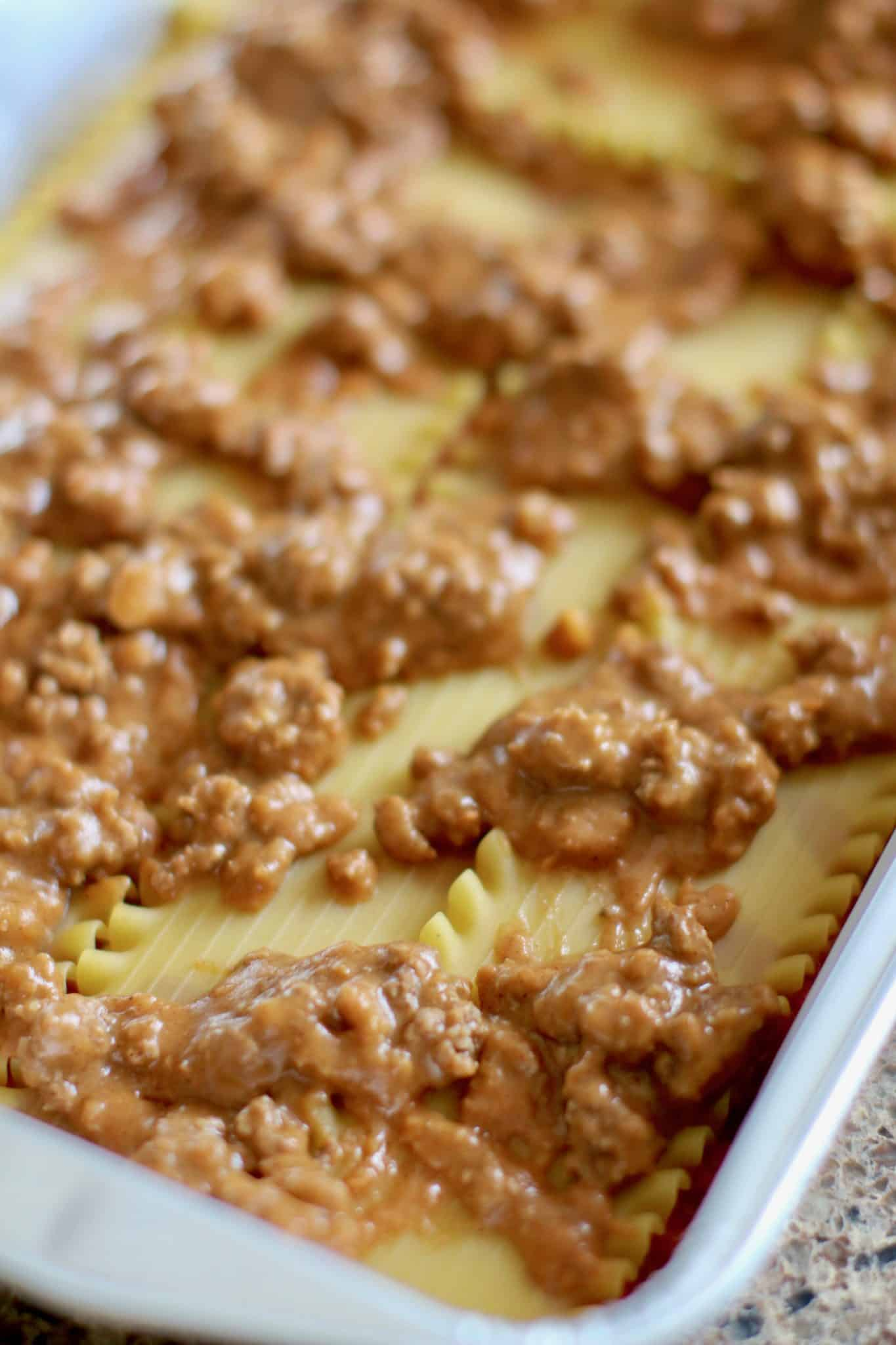 ground beef and refried beans on oven ready lasagna noodles in a baking dish