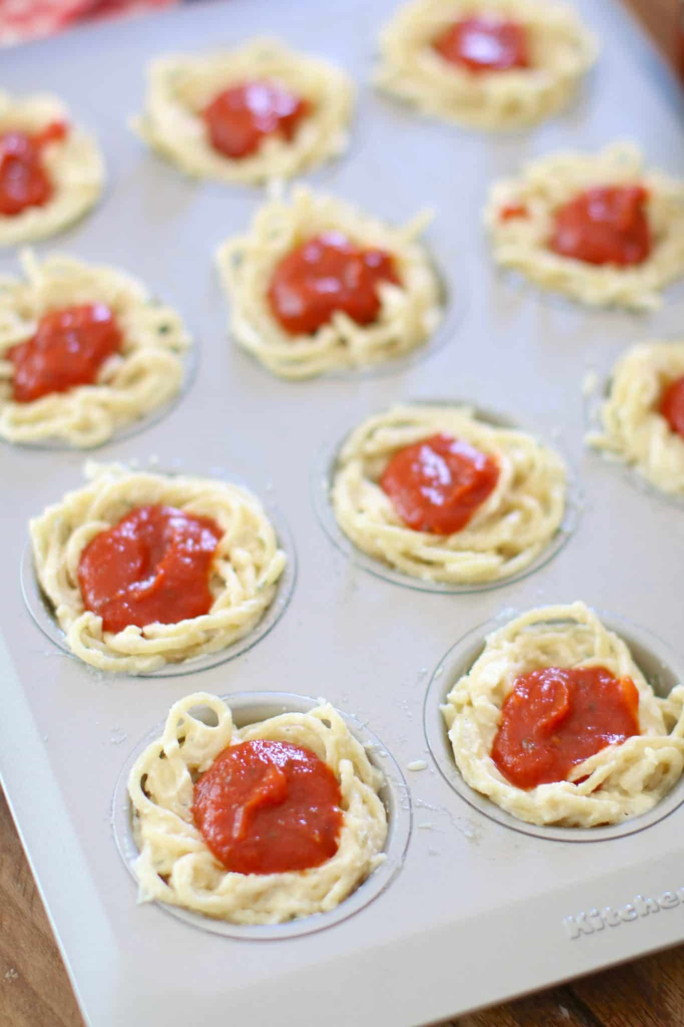 cheesy cooked spaghetti noodles topped with sauce in a muffin pan