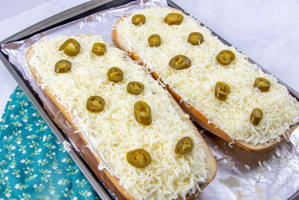 two large slices of Italian Loaf bread topped with cream cheese, shredded mozzarella cheese and sliced jalapenos