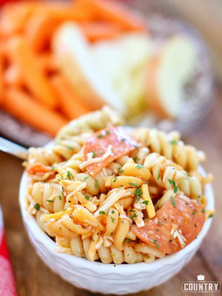 bowl of pasta salad with rotini noodles, cheese, pepperoni and Italian dressing