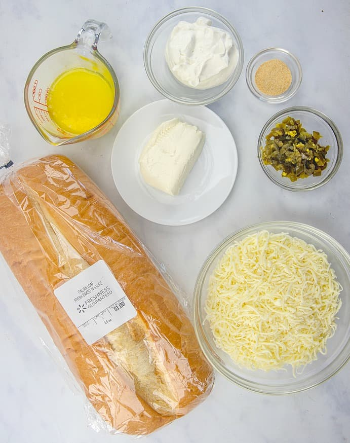 Pão italiano, alho em pó, creme de leite, cream cheese, pimentão jalapeño, queijo mussarela e manteiga