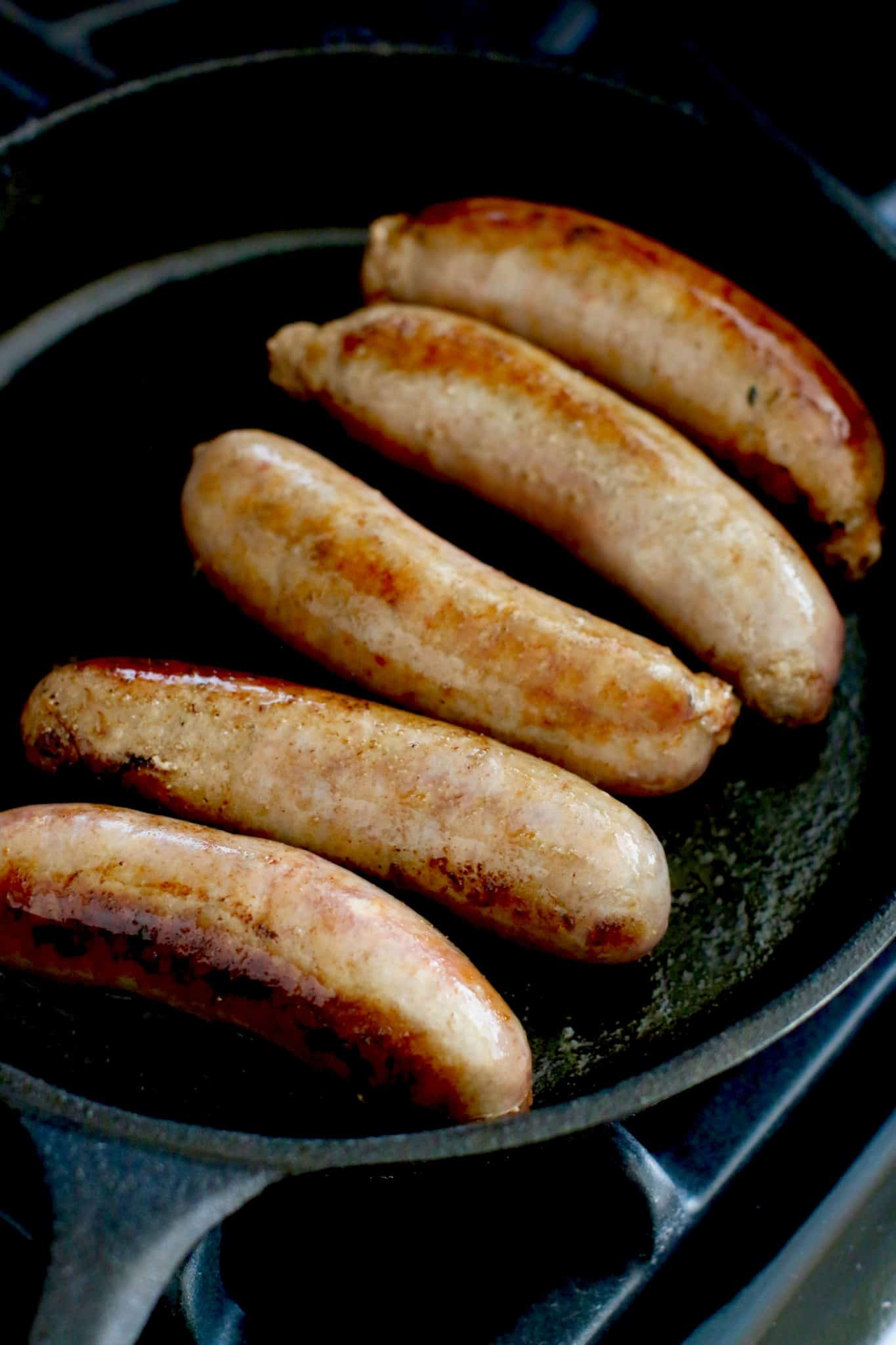 cooking Italian sausage links in a cast iron skillet