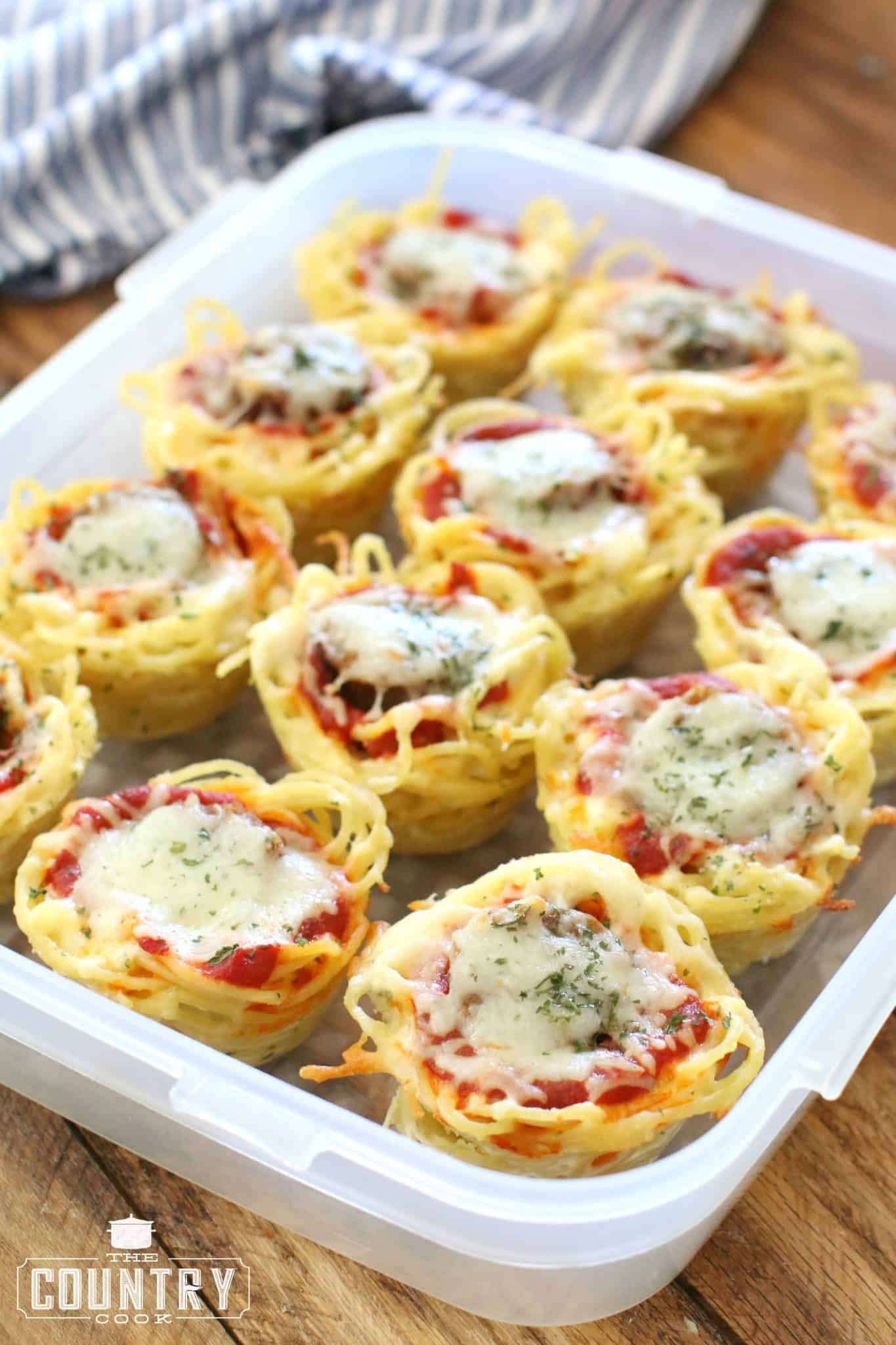 spaghetti sausage cups with melted cheese placed into a plastic container to store in the refrigerator