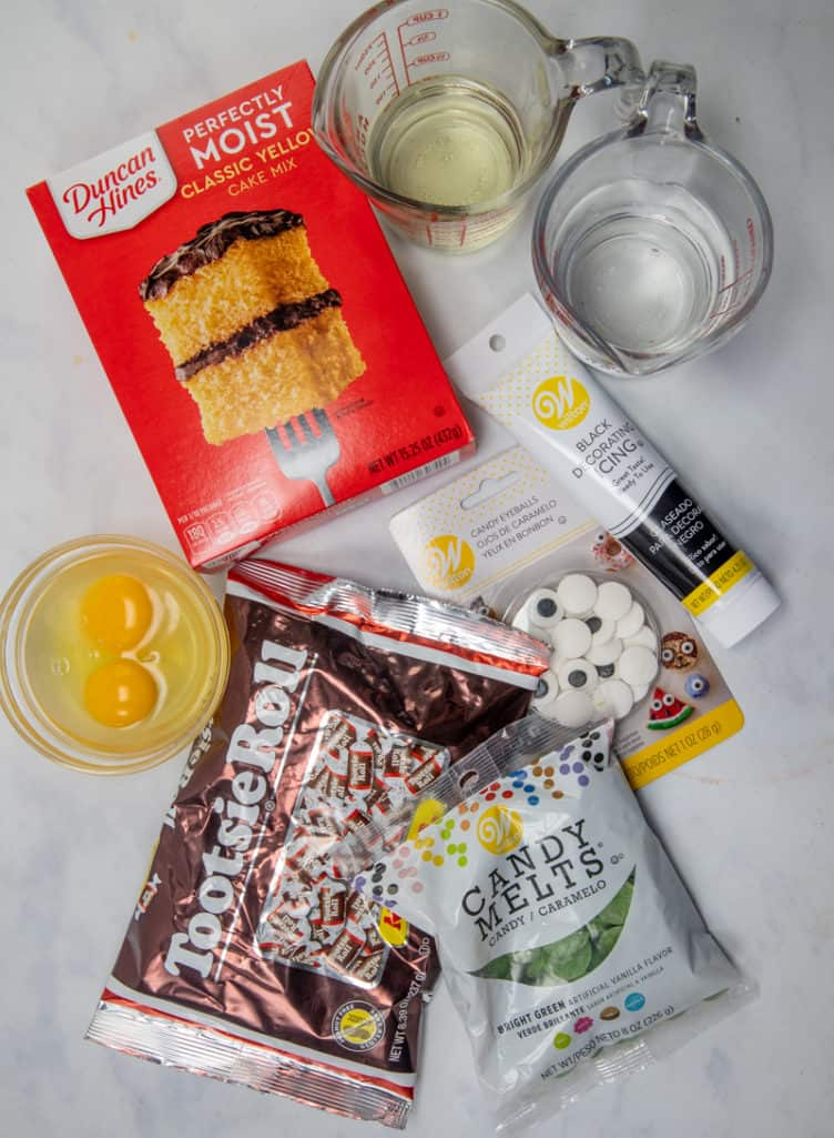 cake mix, eggs, water, vegetable oil, green candy melts, black ready-to-use icing, candy eyeballs, Tootsie Rolls
