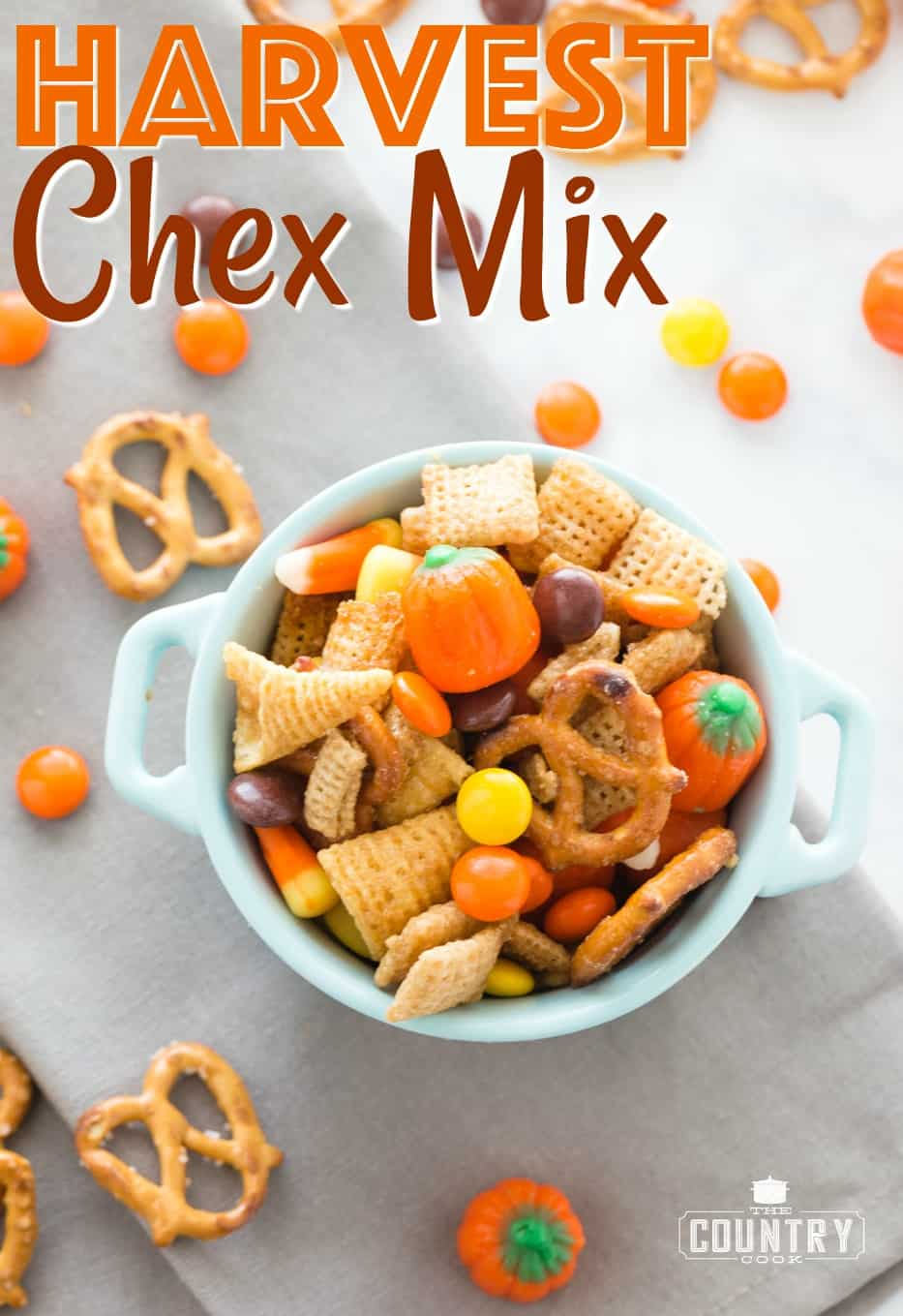 Harvest Chex Mix recipe from The Country Cook. Chex mix shown in a small white bowl with pretzels and Reese's pieces candy scattered around it.