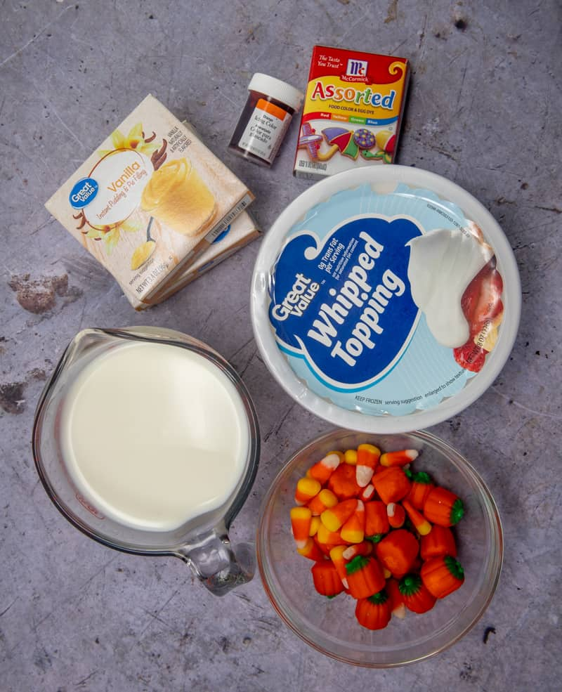 instant vanilla pudding, cold milk, yellow food coloring, orange food coloring, frozen whipped topping, (COOL WHIP), candy corn and pumpkin candy