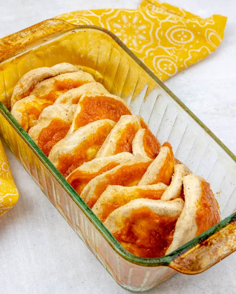 stacked biscuits and pumpkin mixture in a bread loaf pan