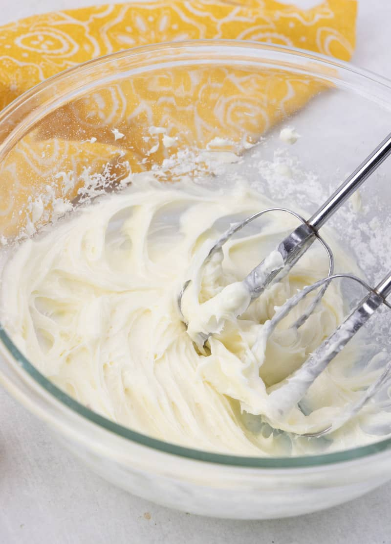 making cream cheese frosting using an electric mixer in a glass bowl