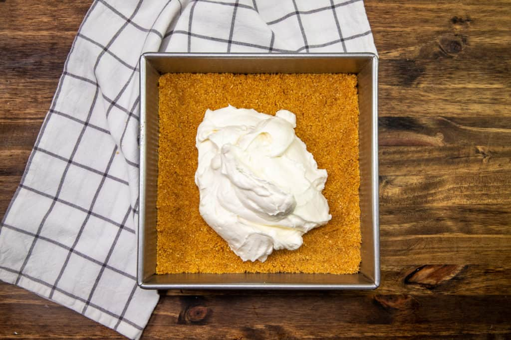 cream cheese and whipped cream mixture spread on top of graham cracker crust in baking pan