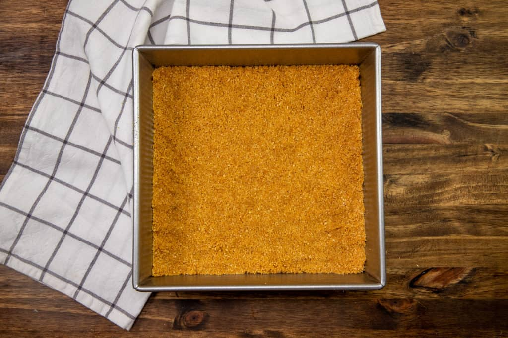 graham cracker crust mixture spread into the bottom of a 9 by 9 inch metal baking pan