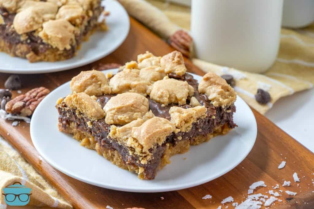 Fudge-filled peanut bars, slice on a white plate with a jar of milk in the background