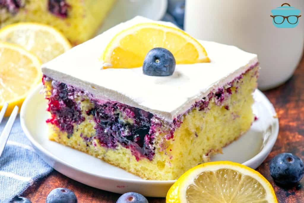 Lemon Blueberry Poke Cake slice on a white plate surrounded by fresh blueberries