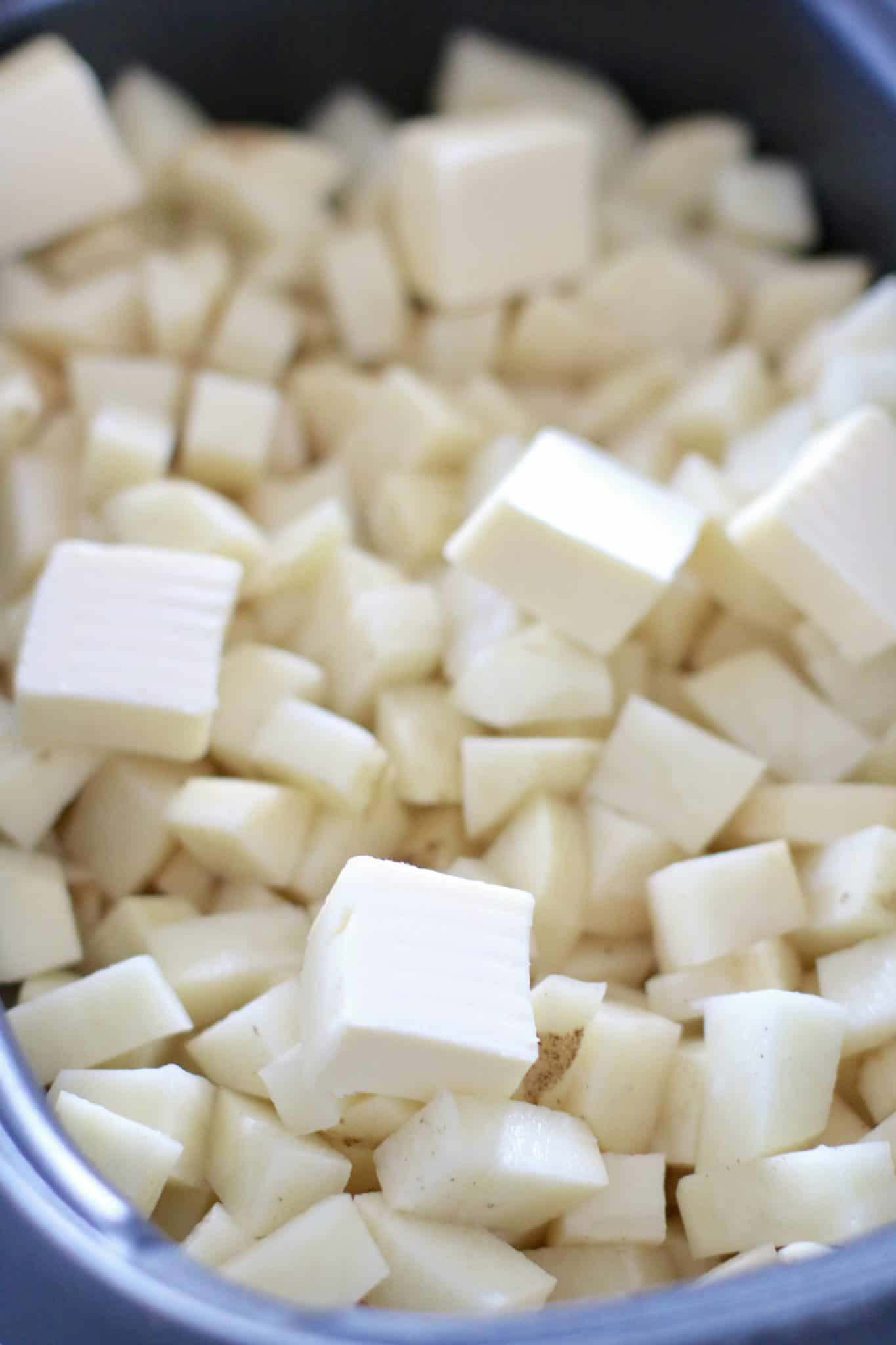 big slices of butter shown on diced potatoes in a slow cooker.