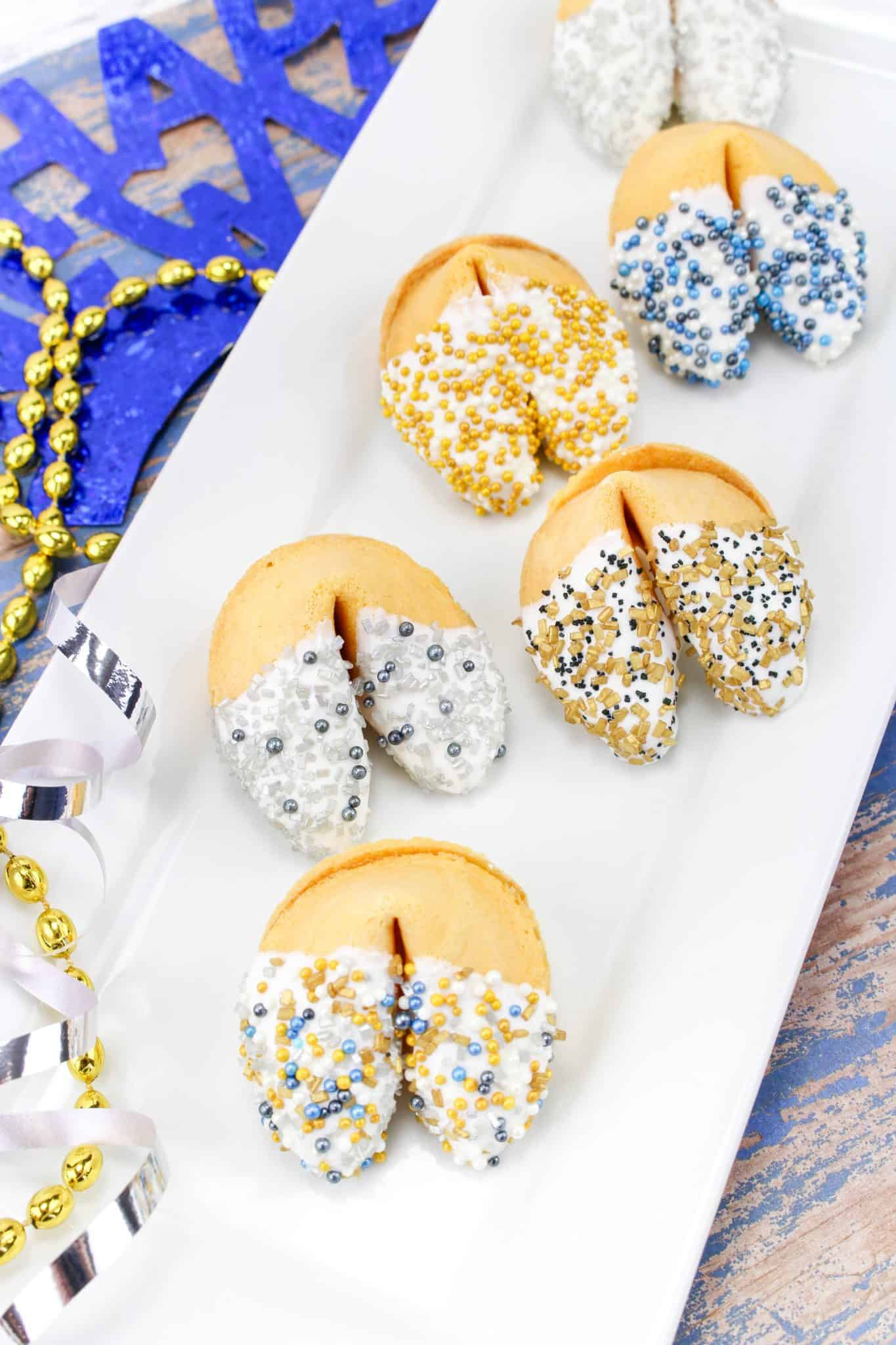 New Year's Eve Chocolate Dipped Fortune Cookies with assorted colored sprinkles on a white plate.