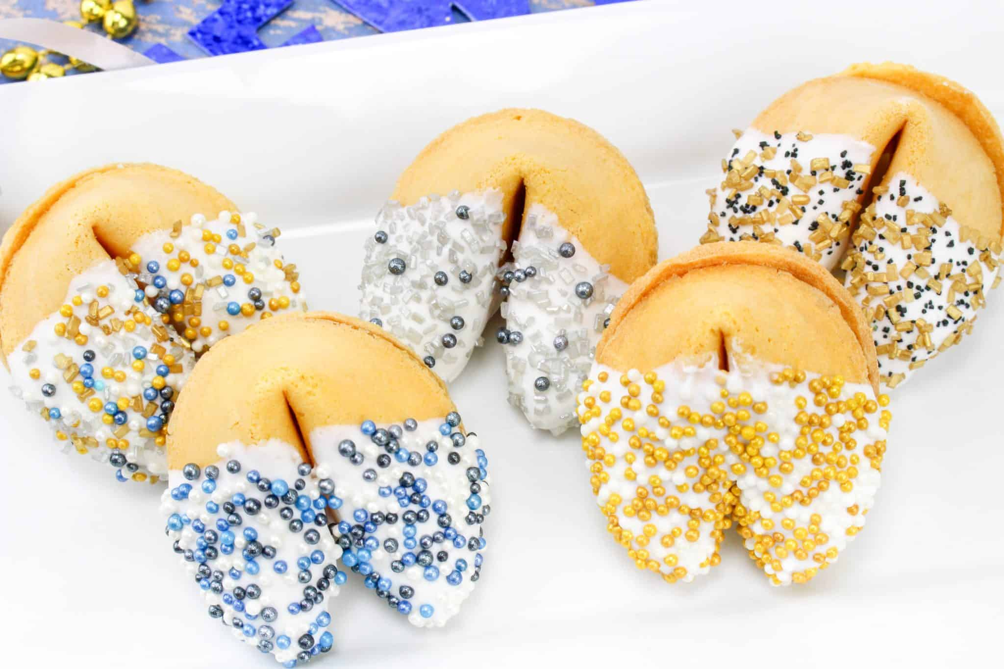 white chocolate dipped fortune cookies for New Years Eve party shown displayed on a long white platter.