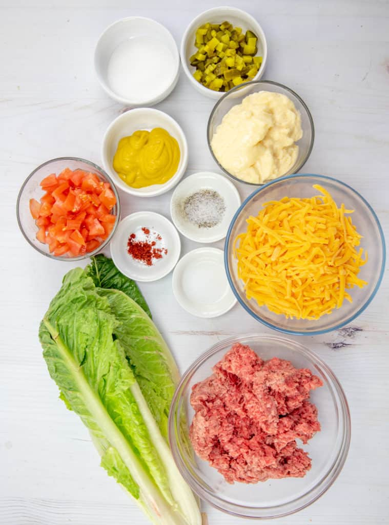 ground beef, salt, pepper, 1 head romaine lettuce, diced tomatoes, shredded cheddar cheese, diced dill pickles, ingredients for thousand island dressing